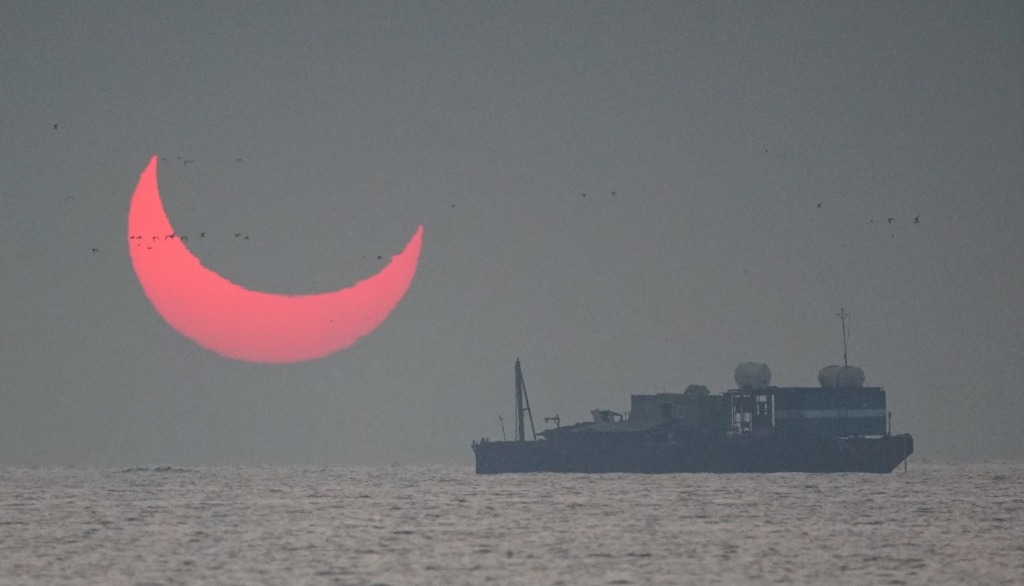 """The sun, partially blocked by the moon, rises above the sea in Al Wakrah, Qatar, Dec. 26, 2019. Facebook and Twitter users were quick to draw comparisons between the reddened partial eclipse to """"devil horns."""""""