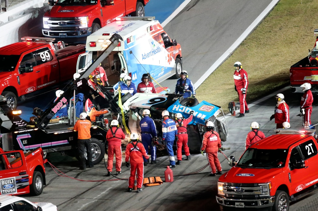 Rescue aid Ryan Newman after he was involved in a wreck on the last lap of the NASCAR Daytona 500 auto race at Daytona International Speedway, Monday, Feb. 17, 2020, in Daytona Beach, Florida. Newman had been in the lead for the last lap when another car's bumper caught his and flipped him.